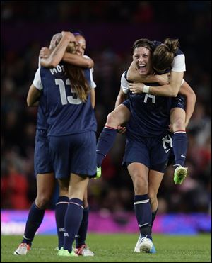 The United States' Abby Wambach, center right, celebrates with teammates including her teammate Kelley O'Hara on her back and scorer of the winning goal Alex Morgan, left with back to camera, after their semifinal win over Canada in their women's soccer match today at the 2012 London Summer Olympics.
