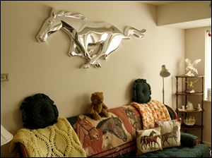From the blankets to the pillows to the chrome art of the Ford Mustang trademark, Lynn Burns' living room in West Toledo is full of horses.