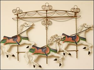 A metal sculpture of carousel horses dance on the wall.