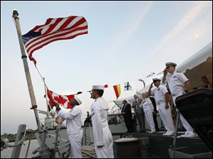 U.S. Navy Seaman Carl Onyewu, left, lowers the U.S. flag during a reception aboard the U.S. Navy frigate USS De Wert as the crew of the Canadian frigate Ville de QueŽbec lowers their flag, in background.
