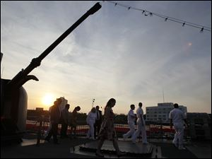 The sun sets as party goers tour the U.S. Navy frigate USS De Wert.