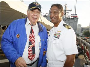 William De Wert, a former Marine, left, talks with Commander Joseph Thomas, commanding officer of the U.S. Navy frigate USS De Wert, during a reception aboard the U.S. Navy frigate in Toledo. The ship, named for William's brother Richard, was in port for Navy Week and the commemoration of the bicentennial of the War of 1812. Richard De Wert was posthumously awarded the Medal of Honor for his heroism while serving with the 7th Marines during the Korean War.