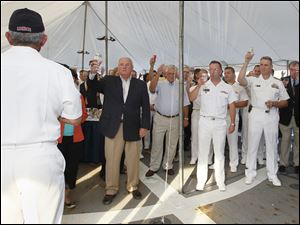Rear Admiral Greg Nosal, back to camera, left, asks guests to raise their glasses and toast servicemen who could not be there.