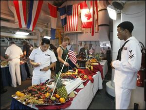 U.S. Navy Culinary Specialist 2nd Class Michael Stephens, right, watches guests get their food during a reception aboard the U.S. Navy frigate USS De Wert.