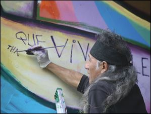 Well-known artist Mario Torero works on one of the first murals in 2010.
