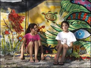 Neighborhood girls Miranda Nino, 9, left, and Micaela Serratos, 11, painted the steps they are sitting on for a mural on the corner of Jervis and Broadway .