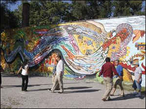Members of the Organization of Latino Artists gather their main mural of a feather serpent that symbolizes one of the gods in the Aztec culture.