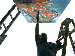 Gordon Ricketts, director of the Arts Village at Bowling Green State University, paints a part of a mural in the Old South End.
