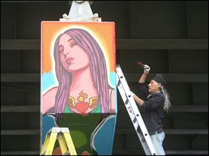 Mario Torero works on the final section of the mural on the I-75 overpass on Broadway and Logan streets.