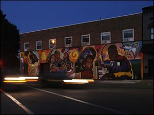 A mural by BGSU students in the 1200 black of Broadway represents local people.