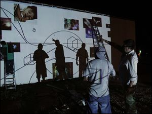 Alberto Marin, right, directs volunteers as they trace a mural from a projected image onto a building wall at the corner of Western and Broadway.