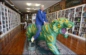 Dorinda Shelley sits atop the green-and-yellow tiger statue in her bookstore, Library House Books and Art. Her passion for books led her to open the store, and a history-themed book shop is set to open this month.