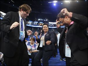 North Carolina delegates Sam Spencer, left, Gwen Wilkins and Roy Sanyal dance as they arrive on the floor.