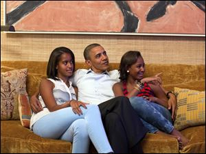In a handout photo, President Barack Obama and his daughters, Malia, left, and Sasha, watch the 2012 Democratic National Convention on TV from the Treaty Room of the White House in Washington.