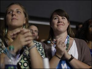 Delegates listens as first lady Michelle Obama addresses the Democratic National Convention.