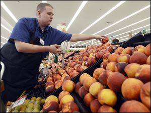 Caleb Tollefson stocks a display of nectarines and peaches at a Hy-Vee grocery store in Sioux Falls, S.D.  The Midwest drought has made corn, soybeans, and other grains much more expensive.