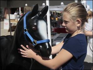 Amelia White, 9, of Waterville, with a plastic horse at the Serenity Farm, Inc. of Northwest Ohio table at the festival. Serenity Farms offers equine assisted learning and a therapeutic riding program at their farm in Luckey, Ohio.