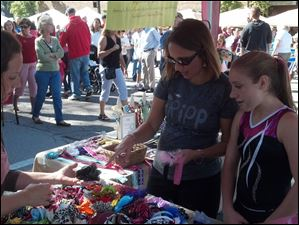 Melissa Lewicz, center, of Perrysburg, and her daughter Bailey, right, look over the hair bows made by Sara Young, left, at Harrison Rally Day on Saturday, Sept. 15, 2012, in downtown Perrysburg. Ms. Young sells baby accessories and shower gifts through her business Raining Babies.