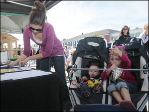 Sarah Brossia, of Perrysburg, left, signs up for a chance to win a gift certificate at the Signature Harley-Davidson of Perrysburg table while her children Graham, 10 months, and Madalynn (cq), 3.5. wait.  A festival brings out a crowd in downtown Perrysburg.