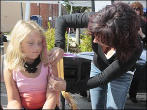 Sophie Perez, 6, of Perrysburg, receives a colored hair extension from Jamie Vanderbilt, of Visions Salon and Spa of Perrysburg.  A festival brings out a crowd in downtown Perrysburg.