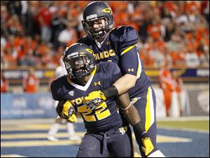 Toledo running back David Fluellen, 22, celebrates with teammate Zac Rosenbauerafter scoring a touchdown during the second quarter of the Rockets' football game against Bowling Green at the Glass Bowl in Toledo.
