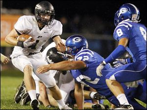 Perrysburg quarterback Steve Slocum (1) runs the ball against  Anthony Wayne's Mike Deck (72) and Hunter Johnson (8).