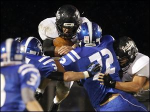 Perrysburg running back Trenton Demmerling (27) leaps for yardage.