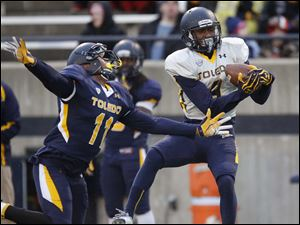 Toledo Rockets gold team receiver Alonzo Russell catches a pass in front of blue team cornerback Cheatham Norrils.