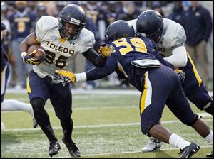 Toledo Rockets gold team running back Ricky Pringle runs past blue team linebacker Alvin Fletcher to score a touchdown.