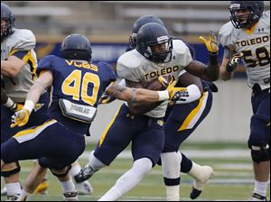 Toledo Rockets gold team running back David Fluellan eludes the grasp of blue team linebacker Trent Voss.