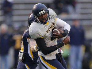 Toledo Rockets gold team quarterback Terrance Owens is grabbed by blue team linebacker Trent Voss.